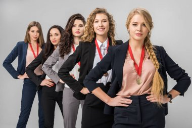 selective focus of beautiful businesswomen standing with medals isolated on grey