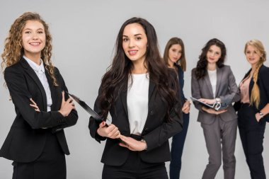 selective focus of cheerful businesswoman holding clipboard near colleague with attractive coworkers standing on background