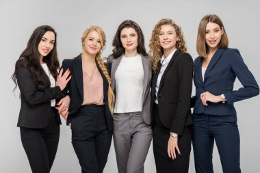 beautiful young businesswomen standing and smiling isolated on grey