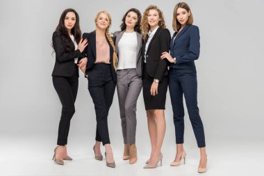 beautiful young businesswomen standing and smiling on grey background