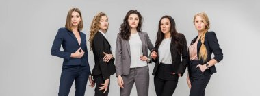 beautiful successful women standing with hands in pockets isolated on grey