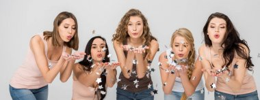 happy girls blowing on confetti stars isolated on grey