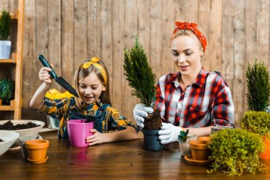 cheerful woman transplanting green plant in pot near cute daughter