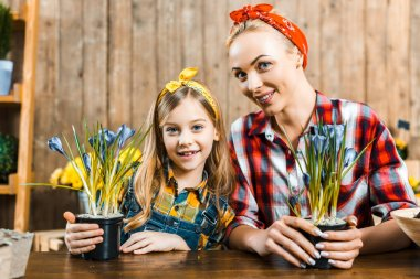 happy mother and adorable daughter looking at camera while holding pots with flowers