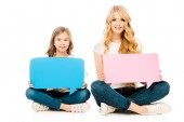 cute child and beautiful mother sitting on floor with crossed legs and holding speech bubbles on white background