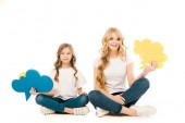 smiling mother and daughter sitting in floor with crossed legs and holding speech bubbles on white background
