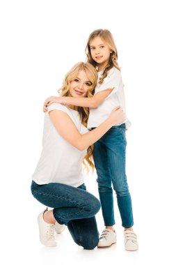 Beautiful woman standing on knee and hugging adorable daughter isolated on white stock vector