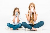mother and daughter sitting on floor with crossed legs and drinking coffee on white background
