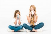 cheerful mother and daughter drinking coffee while sitting on floor with crossed legs on white background