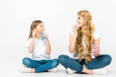 smiling mother and daughter blowing soap bubbles while sitting on floor with crossed legs on white background