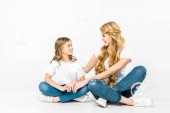 smiling mom and daughter sitting on floor with crossed legs and looking at each other while soap bubbles flying around on white background