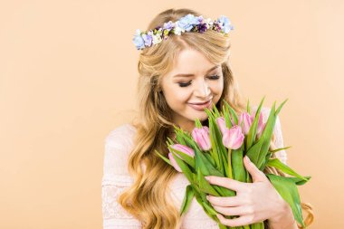 beautiful woman in floral wreath holding bouquet of pink tulips on yellow background