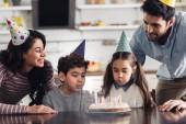 Fotografie niedlichen hispanischen Kinder weht mit Kerzen auf der Geburtstagstorte in der Nähe von glücklicher Vater und Mutter zu Hause