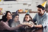 glückliche hispanische Familie in Partymützen, die bei Kerzen auf Geburtstagstorte zu Hause pusten