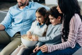 Fényképek cheerful hispanic family watching tv with popcorn bowl at home