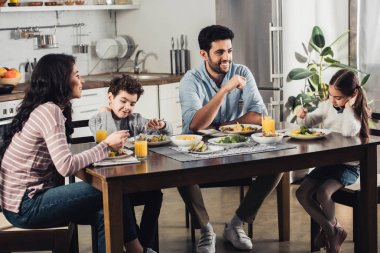 happy latin mother looking at cute daughter having lunch near father and son at home