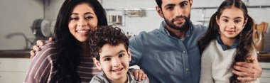 cheerful hispanic family smiling while looking at camera at home