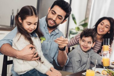 cheerful latin father feeding daughter with broccoli near wife and son at home