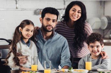 happy hispanic family smiling while looking at camera at home