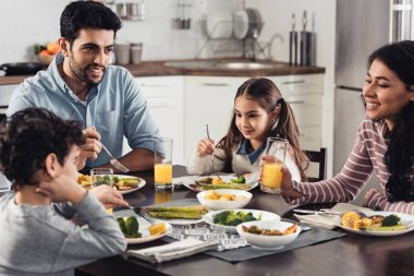 happy hispanic family smiling while having lunch at home