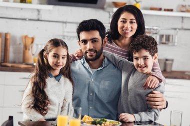 cheerful hispanic family smiling while looking at camera at home