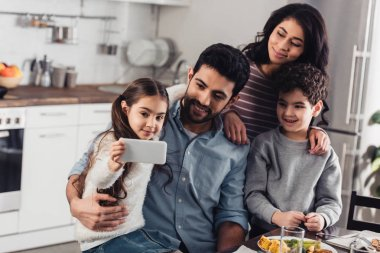 cheerful latin kid taking selfie with hispanic family at home