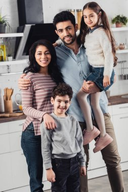 handsome latin father holding in arms cute daughter near wife and son at home