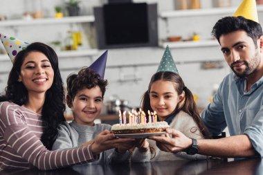 cheerful hispanic family holding birthday cake and smiling at home
