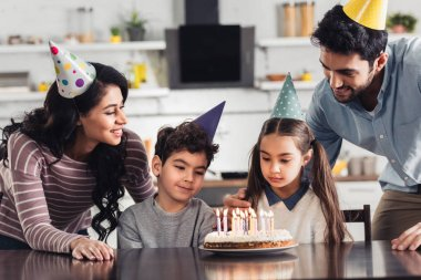 cute hispanic kids looking at birthday cake with burning candles near father and mother at home