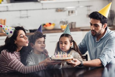 happy hispanic family in party caps blowing at candles on birthday cake at home