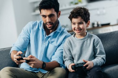 cheerful latin father and son playing video game at home