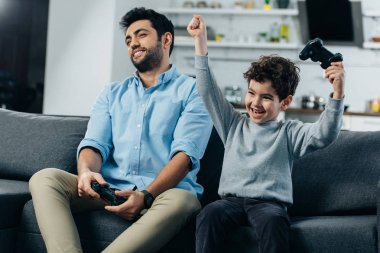 Happy latin kid putting hands above head after playing video game with father at home stock vector