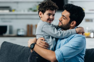 Happy latin father hugging cute son at home stock vector