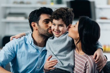 happy latin father and mother kissing cheeks of cute son at home
