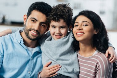 happy latin family hugging while looking at camera at home