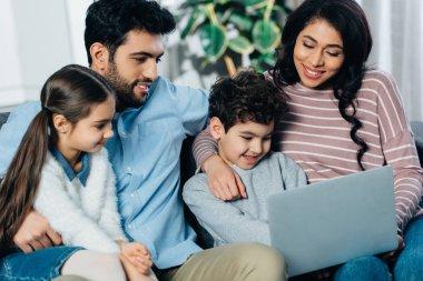 cheerful hispanic family looking at laptop at home