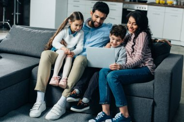 happy hispanic family sitting on sofa and looking at laptop at home