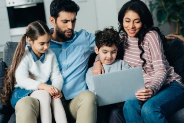 cheerful hispanic family sitting on sofa and looking at laptop at home