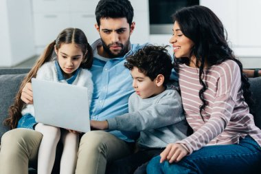 smiling hispanic family sitting on sofa and looking at laptop at home