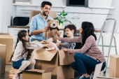 Veselá Latinské otec drží plyšáka poblíž hispánské rodiny při rozbalení krabice v novém domově