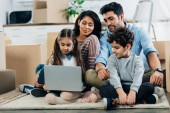 Photo cheerful latino family looking at laptop while sitting on carpet in new home