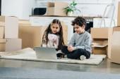 šťastné děti pomocí přenosného počítače, zatímco sedí na koberci v novém domově