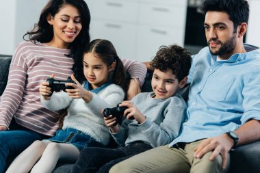 cheerful parents sitting on sofa near kids playing video game at home