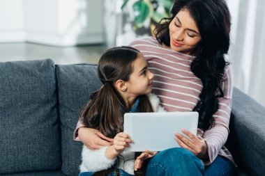 latin woman sitting on sofa and looking at cute daughter while holding digital tablet at home