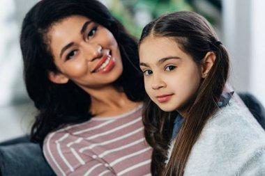 latin woman and cute daughter looking at camera at home