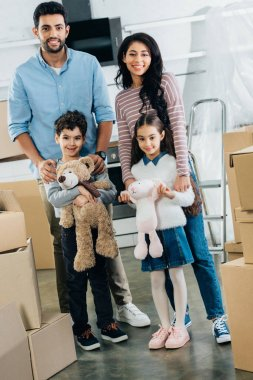 happy latin kids holding soft toys and standing with cheerful mom and dad in new home