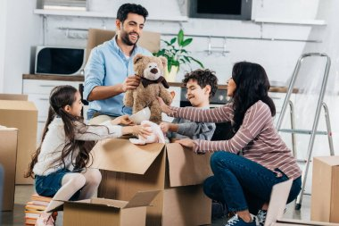 cheerful latin father holding soft toy near hispanic family while unpacking boxes in new home
