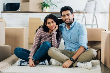 cheerful latin couple sitting with crossed legs near boxes in new home