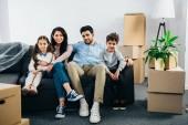 cheerful hispanic family sitting on sofa in new home