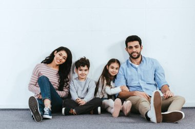 cheerful hispanic family smiling while sitting on floor near white wall